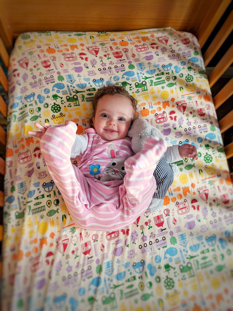 baby at six months old in her cot