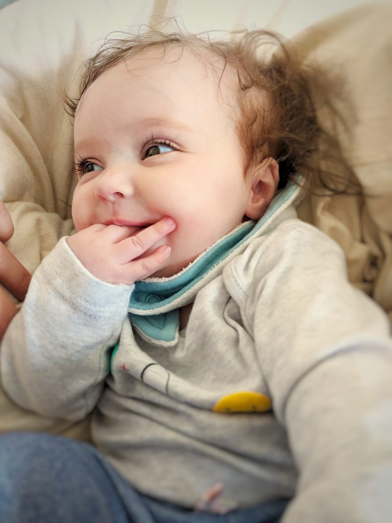happy baby chewing fingers
